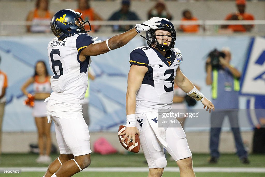 Skyler Howard #3 of the West Virginia Mountaineers celebrates after rushing for a four-yard touchdown against the Miami Hurricanes in the third quarter of the Russell Athletic Bowl at Camping World Stadium on December 28, 2016 in Orlando, Florida. Miami defeated West Virginia 31-14.