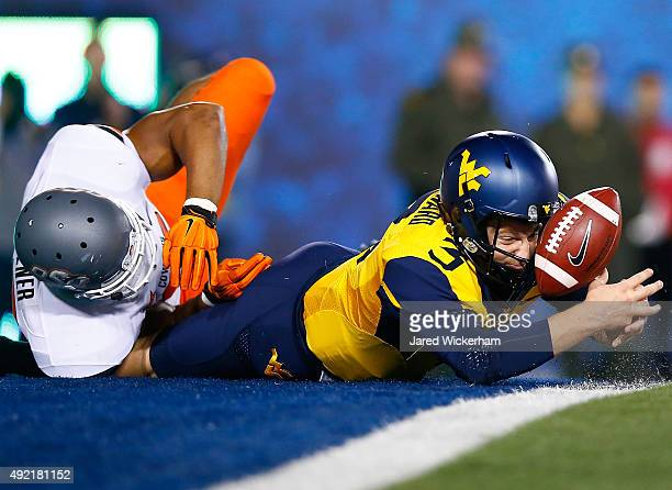 Skyler Howard of the West Virginia Mountaineers fumbles the ball in the endzone in the first half against the Oklahoma State Cowboys during the game...