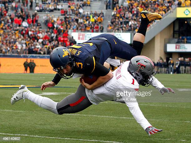 Skyler Howard of the West Virginia Mountaineers is tackled in the first half during the game against Nigel Bethel of the Texas Tech Red Raiders on...