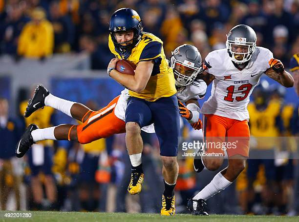 Skyler Howard of the West Virginia Mountaineers tried to evade a flying tackle from Jordan Burton of the Oklahoma State Cowboys in the second half...