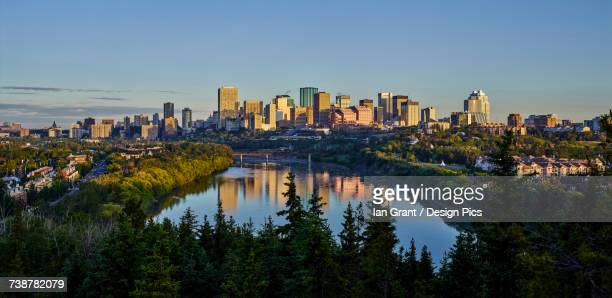 Skyline of downtown Edmonton reflected in the North Saskatchewan River under a blue sky