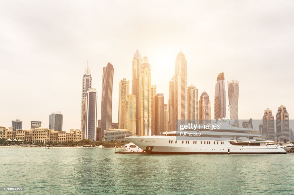 Skyline of Dubai from sea at sunset with a luxury yacht in foreground : Foto stock