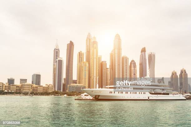 Skyline of Dubai from sea at sunset with a luxury yacht in foreground