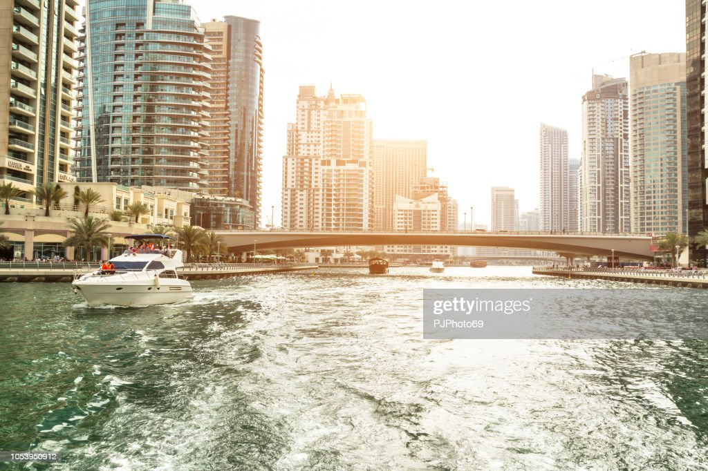 Skyline of Dubai Marina cruising in the channel at sunset with a luxury yacht in foreground on the left with some unrecognizable people : Foto stock