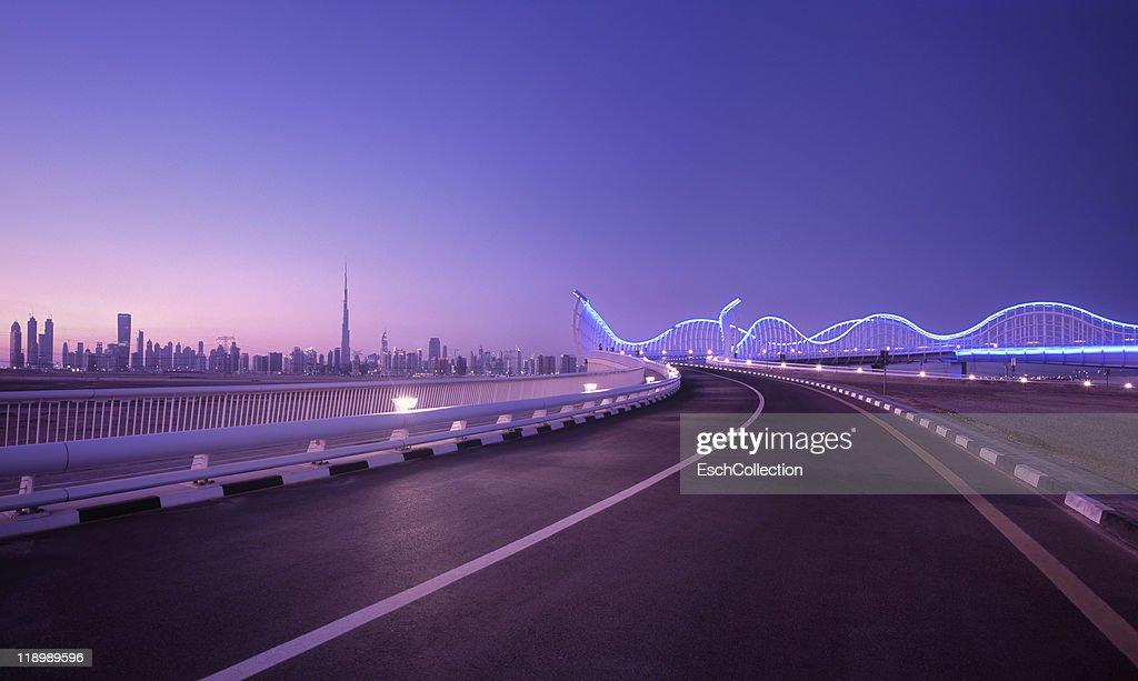 Skyline of Dubai with futuristic bridge, UAE : Stock Photo