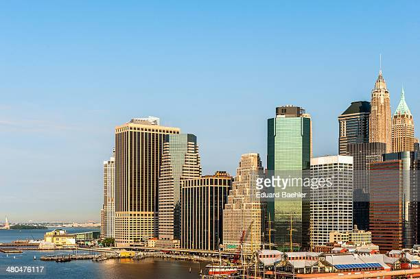 CONTENT] Skyline of financial district Manhattan seen from Brooklyn Bridge under blue sky