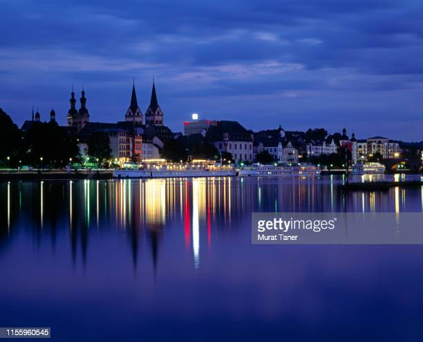 skyline of koblenz at night reflecting into the moselle river - image stock-fotos und bilder