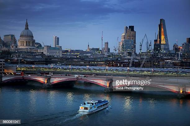 Skyline of London, ferry boat in the Thames river