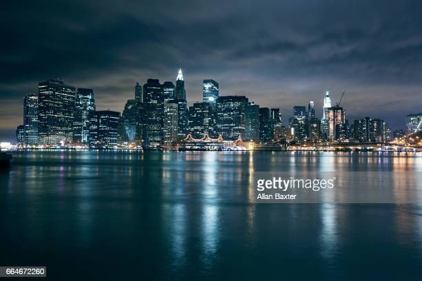 skyline of lower manhattan in new york illuminated at night - horizonte urbano imagens e fotografias de stock