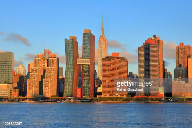 skyline of midtown manhattan with the empire state building at sunrise - rainer grosskopf fotografías e imágenes de stock