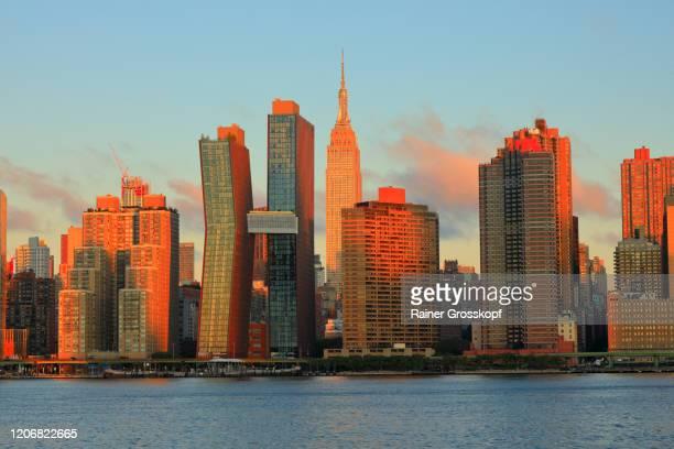 skyline of midtown manhattan with the empire state building at sunrise - rainer grosskopf stock-fotos und bilder