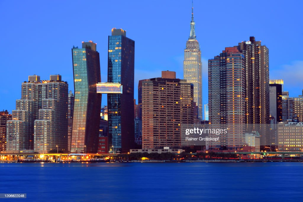 Skyline of Midtown Manhattan with the illumiated Empire State Building at dawn : Stock-Foto