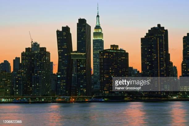 skyline of midtown manhattan with the illumiated empire state building at sunset - rainer grosskopf stock-fotos und bilder
