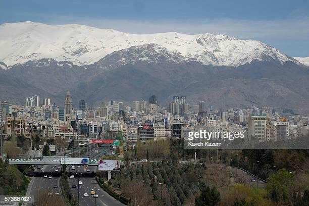 Skyline of north Tehran with hills covered in snow and the high rises scattered around and cars on Modares highway heading to the center seen on...