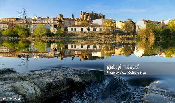 skyline of plasencia with the old cathedral in the background reflected on the surface of river jerte at sunset - victor ovies fotografías e imágenes de stock