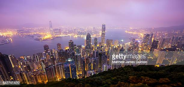 Skyline of skyscrapers in Hong Kong lit up in the early morning before sunrise with bay in background