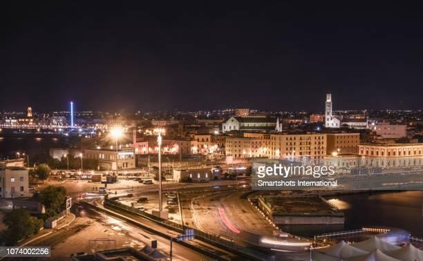 skyline of the city of bari illuminated at night in puglia, italy - bari foto e immagini stock