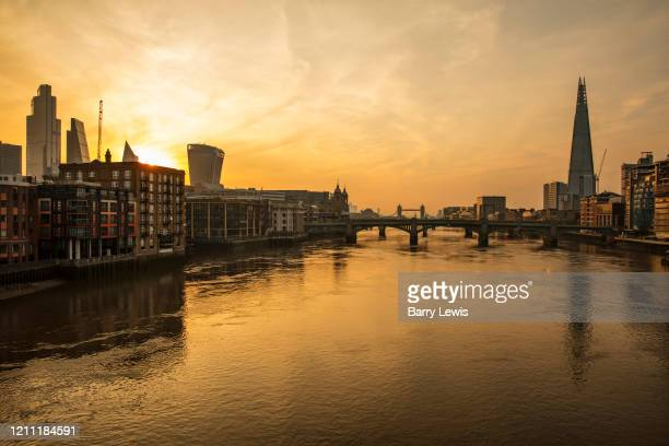 Skyline of the city of London and Tower Bridge taken from the Millenium Bridge at dawn during the coronavirus pandemic on the 24th April 2020 in...