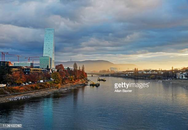 skyline of the 'roche tower' on riverside of the river rhine at sunrise - basel port stock photos and pictures