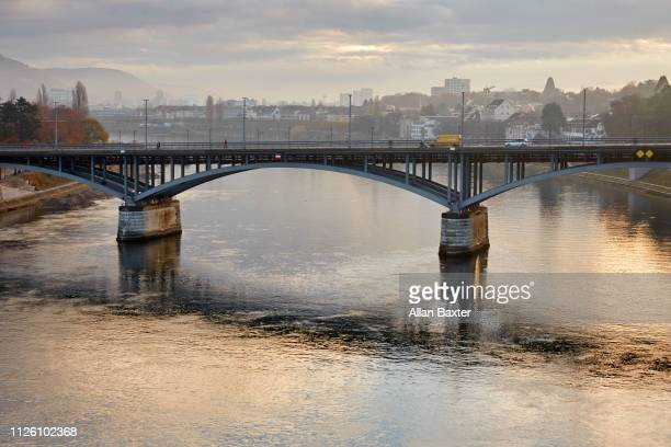 skyline of 'wettsteinbrucke' bridge in basel with river rhine at sunrise - basel switzerland stock pictures, royalty-free photos & images