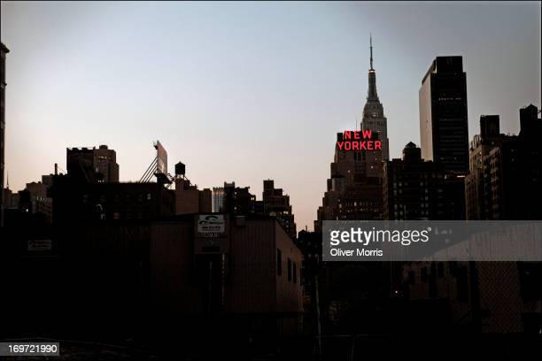 Skyline view highlights the neon sign atop the New Yorker Hotel Manhattan New York New York April 26 2013 The spire of the Empire State Building is...