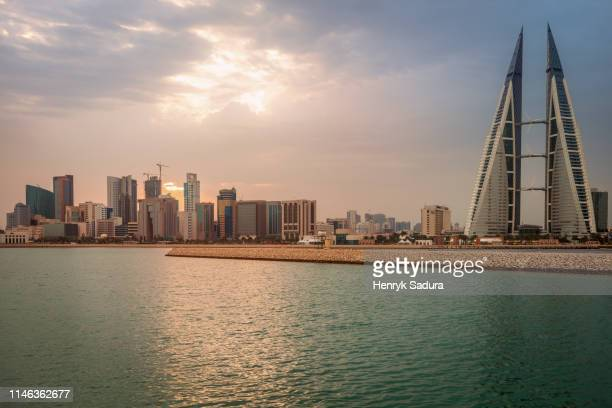skyline with bahrain world trade center in manama, bahrain - bahrain stock pictures, royalty-free photos & images