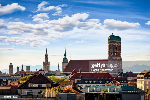 skyline with frauenkirche, st. peter church, new town hall and mountain range in the background, munich, bavaria, germany - münchen stock-fotos und bilder