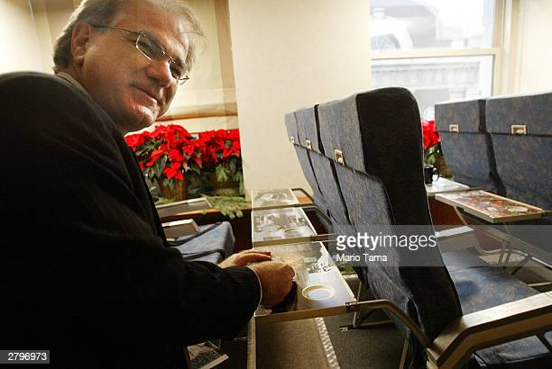 SkyMedia President Nick Pajic demonstrates the new tray table advertising to be installed on America West Airlines planes December 9 2003 in New York...