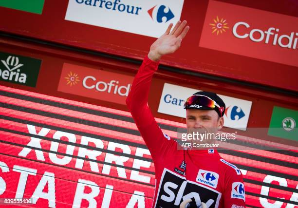 Sky's British cyclist Chris Froome poses on the podium with the leader's red jersey after the 8th stage of the 72nd edition of 'La Vuelta' Tour of...