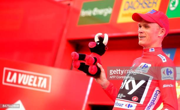 Sky's British cyclist Christopher Froome celebrates on the podium retaining the red jersey after winning the 16th stage of the 72nd edition of 'La...