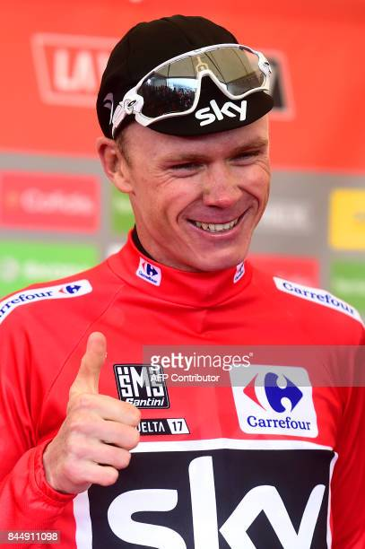 Sky's British cyclist Christopher Froome smiles as he sports the overall leader's red jersey on the podium of the 20th stage of the 72nd edition of...