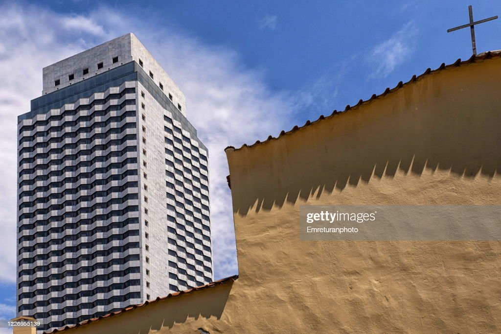 A skyscraper and a church building on a sunny day in Izmir. : Stock Photo