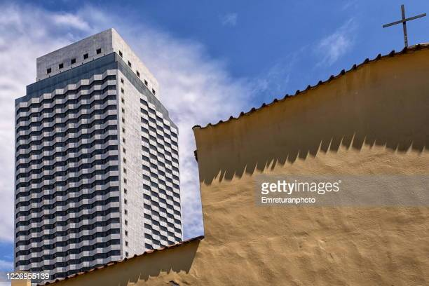 a skyscraper and a church building on a sunny day in izmir. - emreturanphoto stock-fotos und bilder
