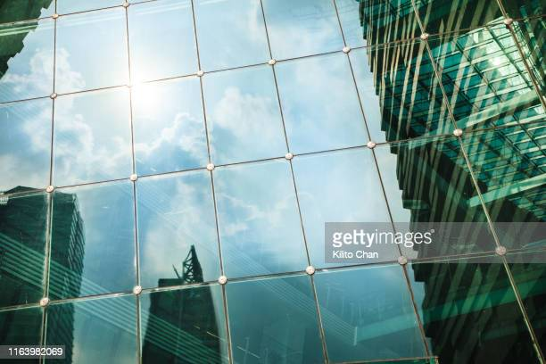 skyscraper and cloudy sky reflections on glass window - asymmetry stock pictures, royalty-free photos & images