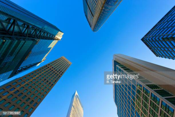 skyscraper array and blue sky in the shiodome district of minato ward in tokyo, japan - image stock-fotos und bilder