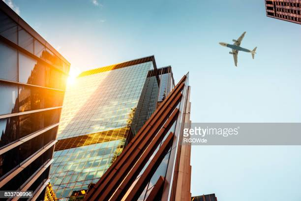 skyscraper with a airplane silhouette - low angle view stock pictures, royalty-free photos & images