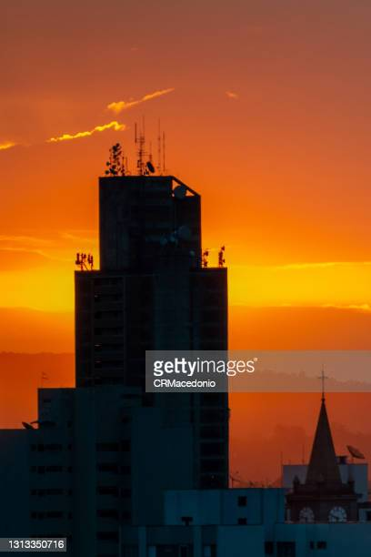 skyscraper with a lot of antennas and the hot and orange sunset. - crmacedonio stock-fotos und bilder