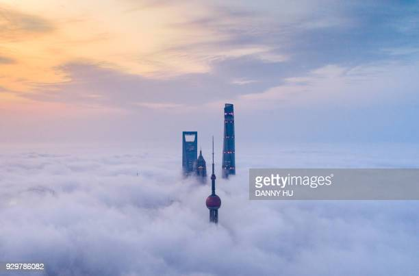 skyscrapers above advection fog in lujiazui, shanghai - international landmark stock pictures, royalty-free photos & images
