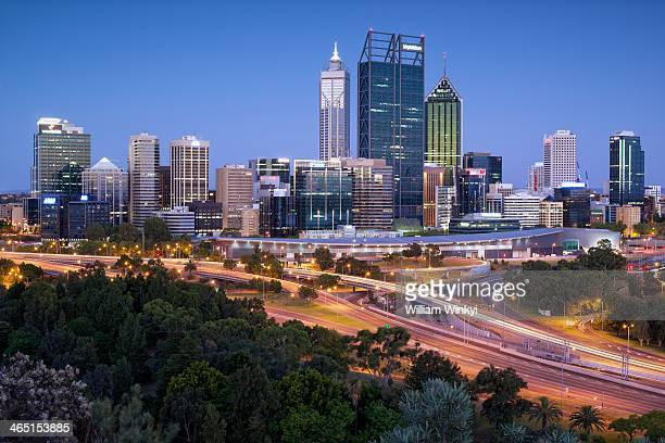 Skyscrapers and buildings stand illuminated at night, seen from Kings Park viewing platform in Perth CBD, Western Australia.