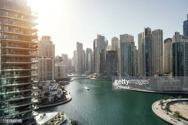 skyscrapers and cityscape at sunset in dubai marina bay. - united arab emirates stock pictures, royalty-free photos & images