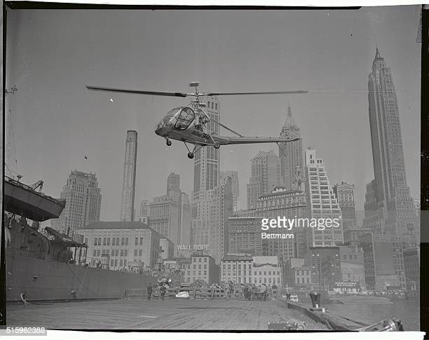 Skyscrapers are backdrop for a Hiller 360 which hovers over skyport at Wall Street and East River at end of first coasttocoast commercial helicopter...