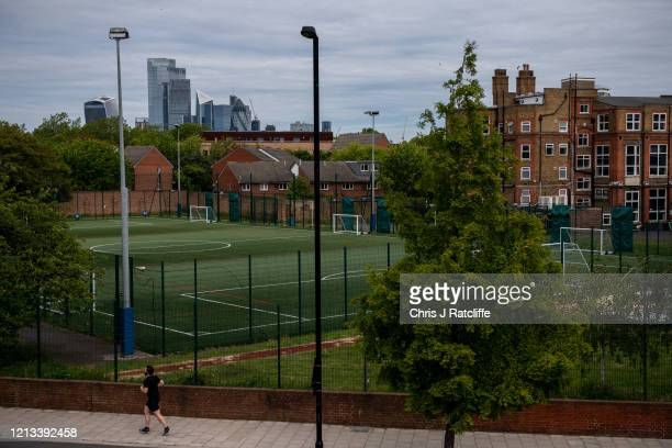Skyscrapers are seen behind empty football pitches at the temporarily closed Harris Academy Bermondsey on May 17, 2020 in London, England. The...