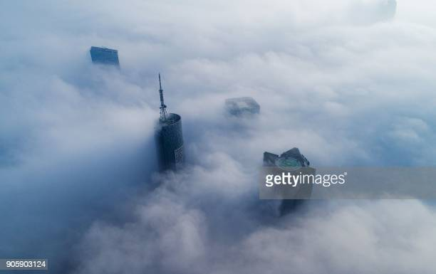 TOPSHOT Skyscrapers are seen shrouded in fog in Hefei in eastern China's Anhui province on January 17 2018 / AFP PHOTO / / China OUT