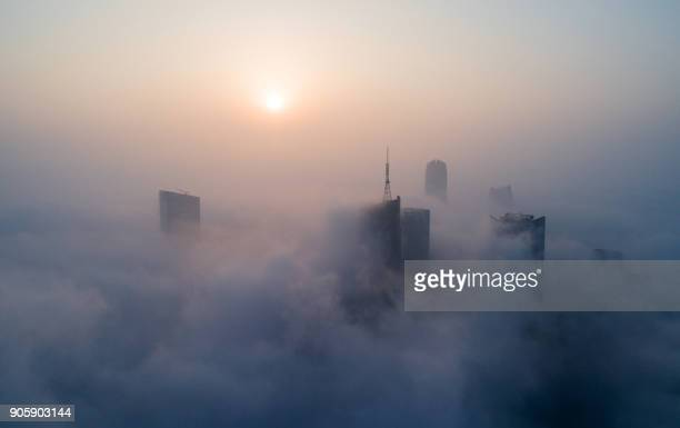 Skyscrapers are seen shrouded in fog in Hefei in eastern China's Anhui province on January 17 2018 / AFP PHOTO / / China OUT