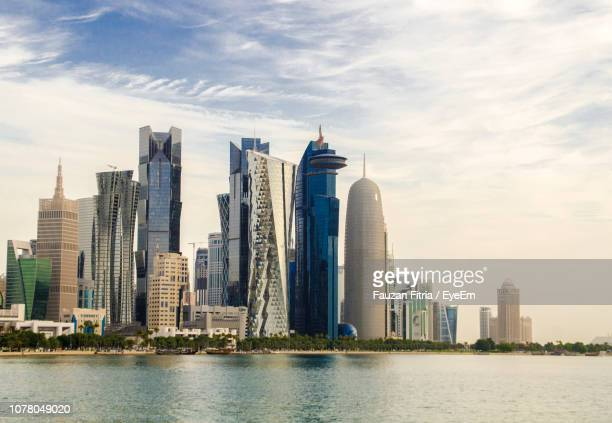 skyscrapers by river against buildings in city against sky - doha stock pictures, royalty-free photos & images