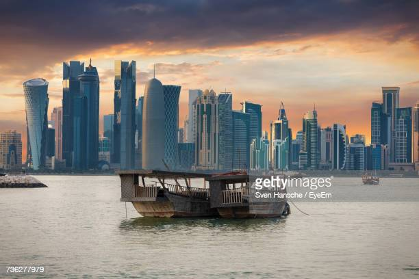 skyscrapers in city at sunset - qatar stock photos and pictures