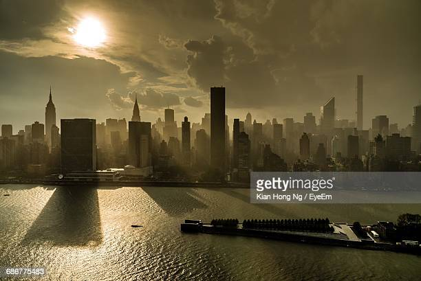 Skyscrapers In Manhattan By East River Against Sky During Sunrise