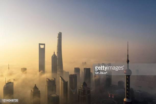 skyscrapers in shanghai city over the advection fog at sunrise - smog stock-fotos und bilder