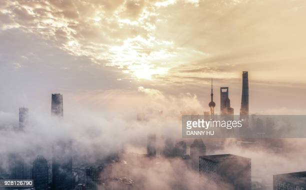 skyscrapers in shanghai city over the advection fog at sunrise - smog china stock-fotos und bilder