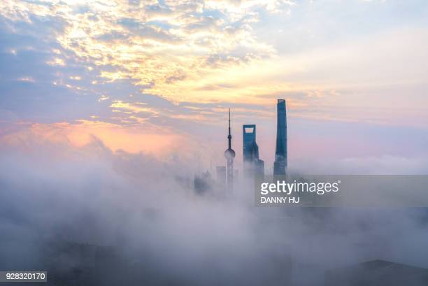 skyscrapers in shanghai city over the advection fog at sunrise - smog stock pictures, royalty-free photos & images